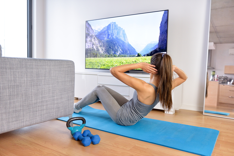 Home workout - woman exercising in front of a flat screen watching a fitness program or exercising during a TV show lying on a yoga mat in front of the sofa in the living room of a house or apartment.