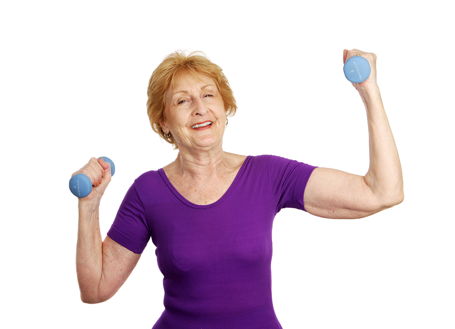 A pretty senior woman smiling as she lifts freeweights. Isolated on white.